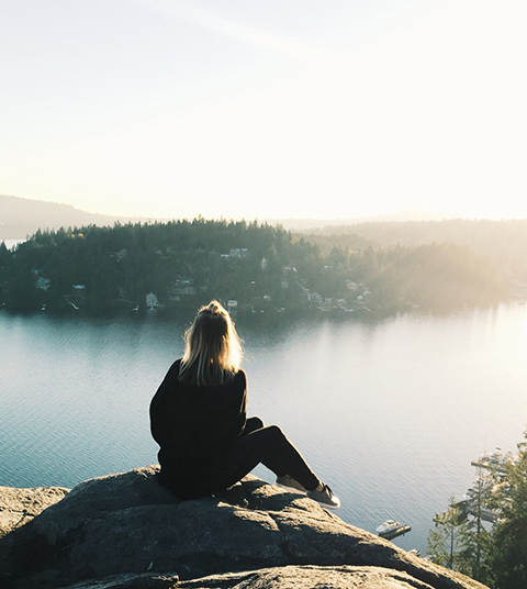 A woman staring at beautiful scenery from the mountain top